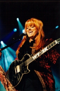 Country legend Wynonna on stage with guitar.
