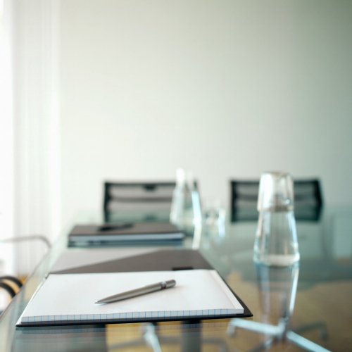 conference table with notepad and water