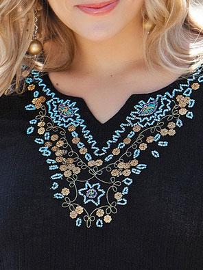 Turquoise beads on a black gauze tunic.