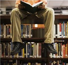 Man sitting on a stack of library books.