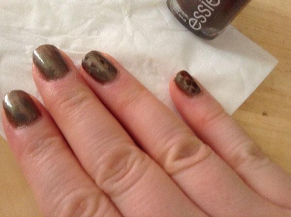 Essie bronze sparkle nail polish on right hand.