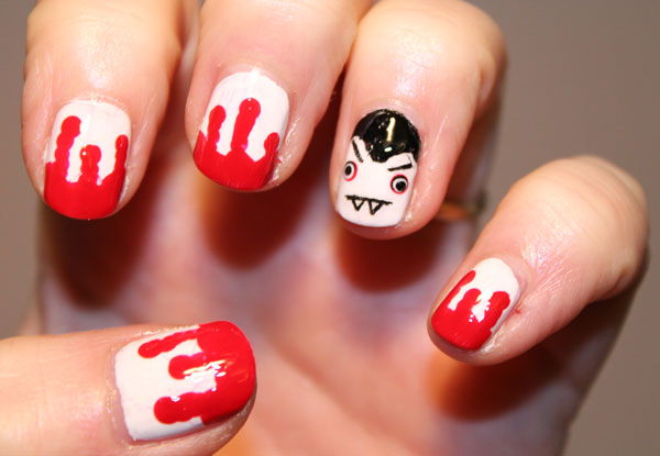 Red bloody nails nail art with vampire accent nail.