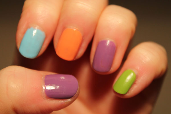A mixture of colored nails polishes on one hand.