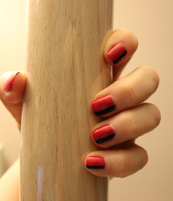 Nails painted with black and red color blocking nail art.