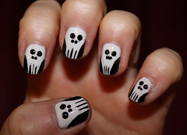 Simple white skull nail art on all five nails.