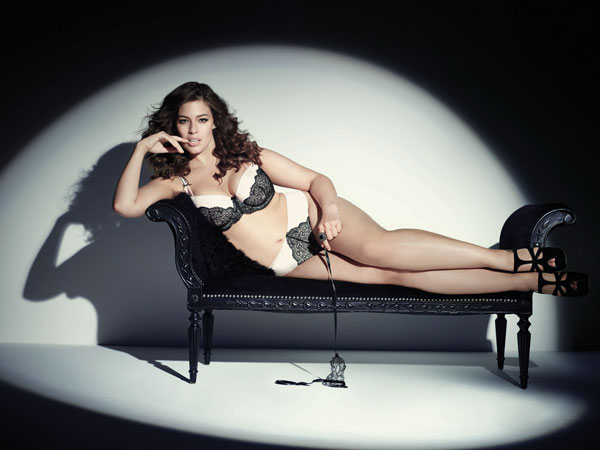 Ashley Graham shows off a pair of plus size bra and panties for Addition-Elle while reclining on a chaise longue.