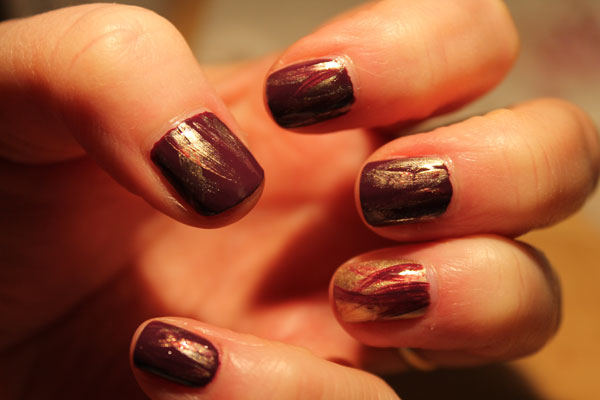 Purple nail polish with gold accent wisps.