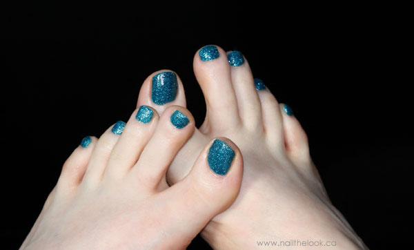 Blue nail polish against a black background.