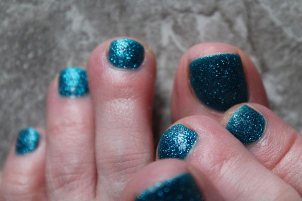 Blue Liberty nail polish against marble floor.