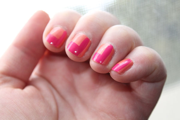 The pink and red nail polish under natural light.