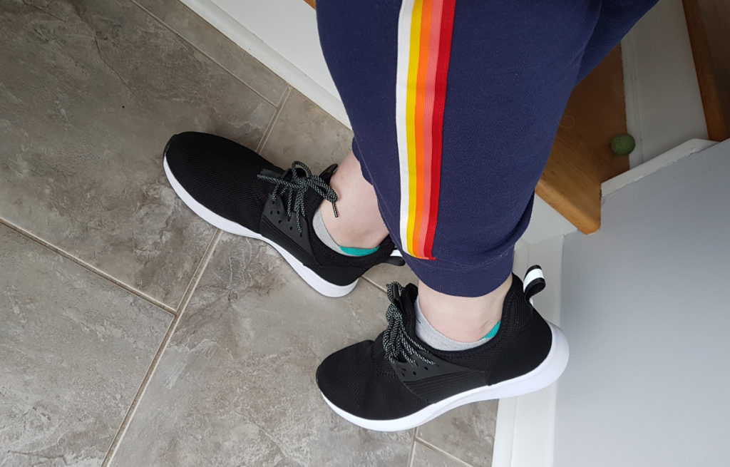 Profile view of fit of black sneakers.